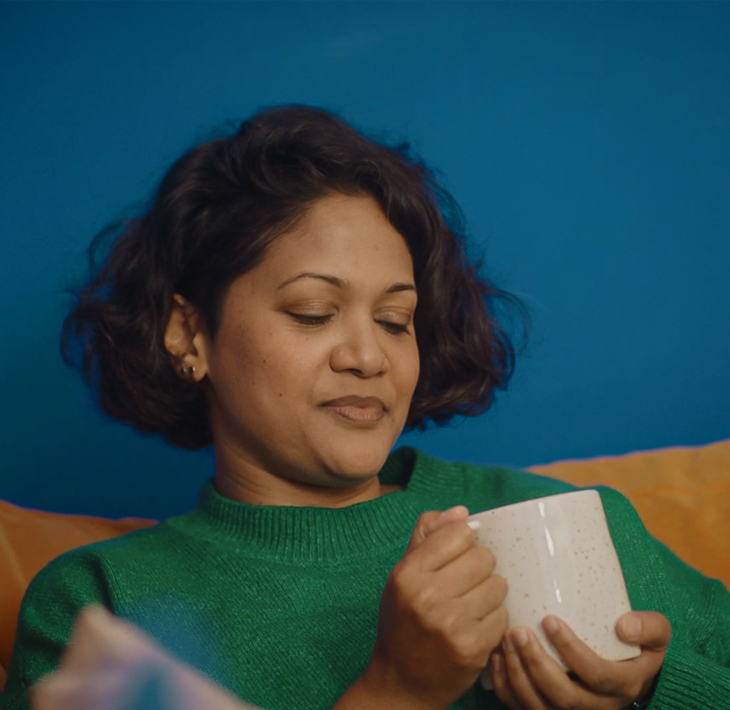 A young woman sat on a sofa looking at a cup of tea she is holding in her hands